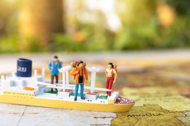 Pessoas em miniatura: viajando com uma mochila em pé no mapa do mundo vintage, viagens e verão conceito. Foto Premium