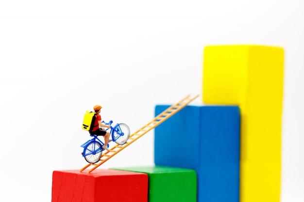 Pessoas em miniatura: viajante andando de bicicleta na escada de madeira com gráfico de crescimento, conceito do caminho para o objetivo e sucesso. Foto Premium