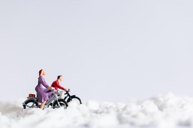 Pessoas em miniatura: viajantes andando de bicicleta na neve Foto Premium