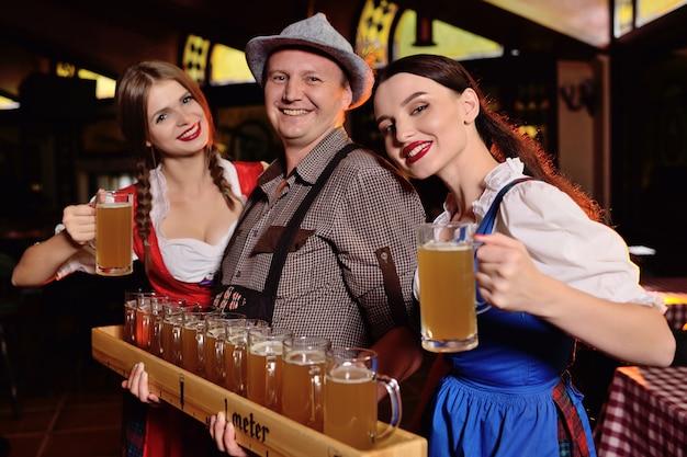 Pessoas em roupas da baviera com uma placa de cerveja e óculos contra um fundo de bar Foto Premium