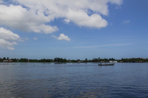 Pessoas em uma canoa no rio com guarda-chuvas Foto gratuita