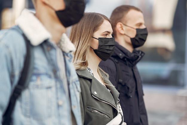 Pessoas em uma máscara fica na rua Foto gratuita