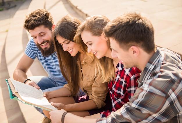 Pessoas engraçadas lêem um livro juntos. Foto Premium