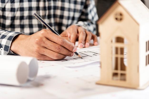 Pessoas escrevendo no fundo e casa de madeira Foto gratuita
