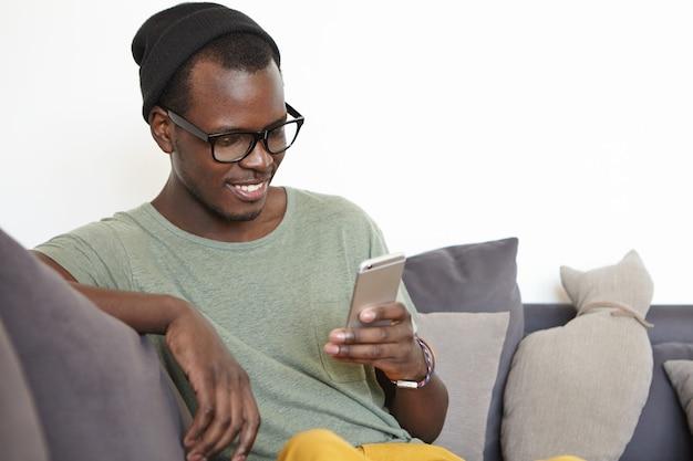 Pessoas, estilo de vida moderno, conceito de tecnologia e comunicação. alegre jovem estudante de pele escura, lendo a mensagem Foto gratuita