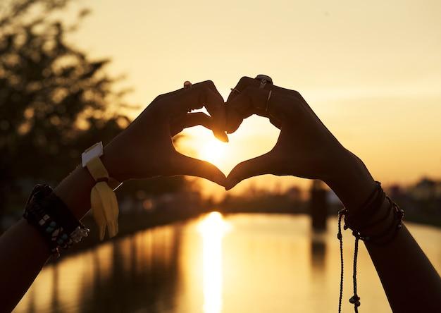 Pessoas fazendo as mãos no pôr do sol de silhueta de forma de coração Foto gratuita