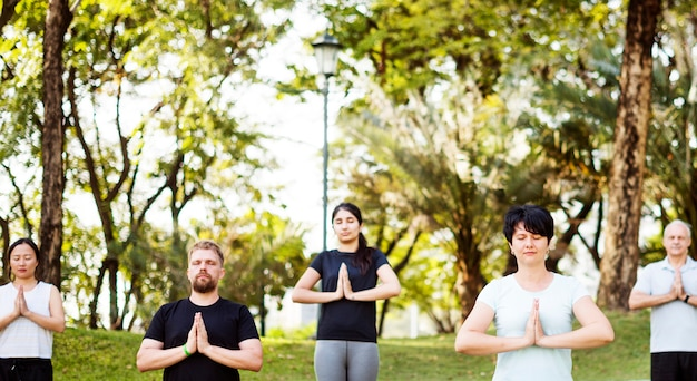 Pessoas fazendo yoga no parque Foto Premium