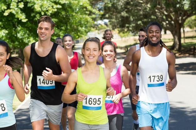 Pessoas felizes correndo corrida no parque Foto Premium
