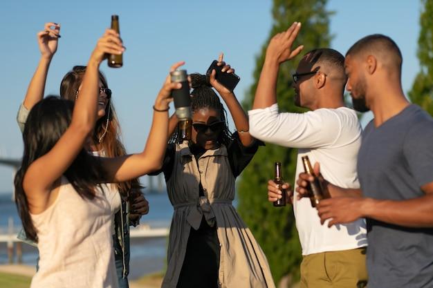 Pessoas felizes dançando com garrafas de cerveja Foto gratuita