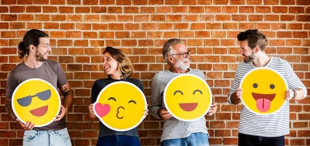 Pessoas felizes segurando emoticons positivos Foto Premium