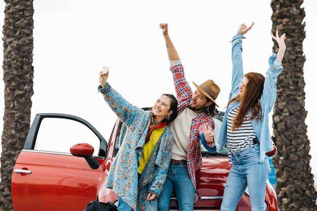 Pessoas felizes tomando selfie perto de carro vermelho na rua Foto gratuita