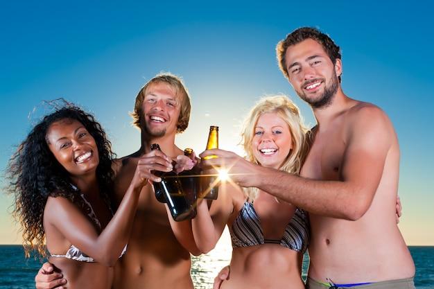 Pessoas festa na praia com bebidas Foto Premium