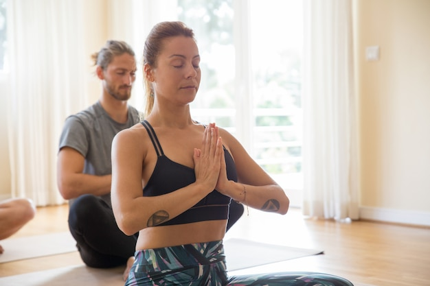Pessoas focadas meditando na aula de ioga Foto gratuita