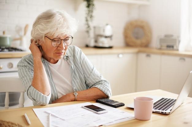 Pessoas, idade, tecnologia e finanças. mulher aposentada deprimida e infeliz, que paga contas domésticas online, se esforçando para sobreviver, sentada à mesa da cozinha, cercada de papéis, usando gadgets Foto gratuita