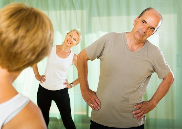 Pessoas idosas em fitness com instrutor Foto gratuita
