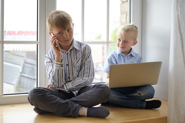 Pessoas, infância, dispositivos modernos e conceito de negócio. dois meninos caucasianos fofos brincando em casa, fingindo ser empresários, sentados no parapeito da janela com roupas formais, usando dispositivos eletrônicos Foto gratuita