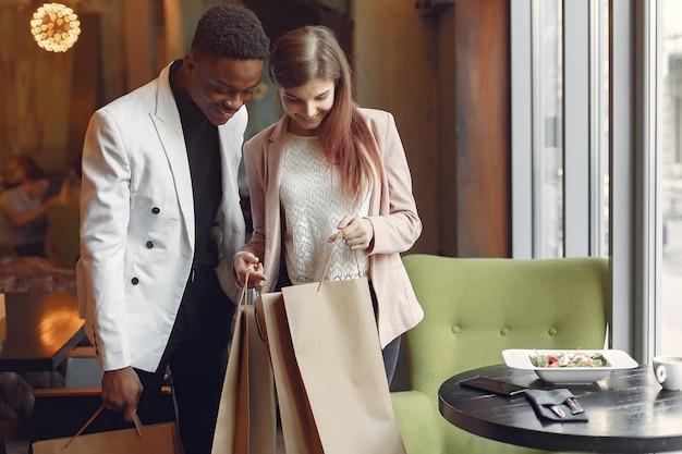 Pessoas internacionais em pé em um café com sacolas de compras Foto gratuita