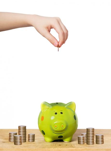 Pessoas mão colocando moedas em um cofrinho. Foto Premium