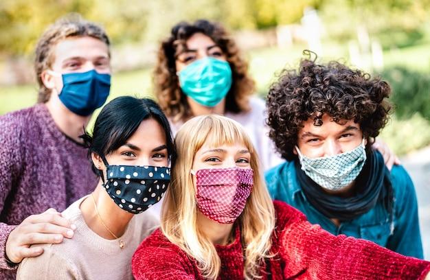 Pessoas multirraciais fazendo selfie usando máscara facial e roupas de primavera Foto Premium