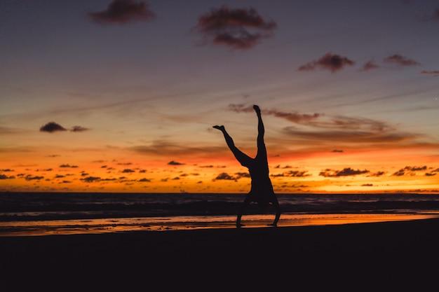Pessoas na costa do oceano ao pôr do sol. homem salta contra o pano de fundo do sol poente Foto gratuita