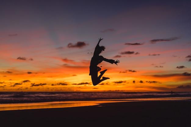 Pessoas na praia ao pôr do sol. a menina está saltando contra o pano de fundo do sol poente. Foto gratuita