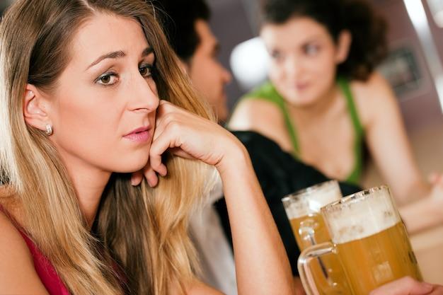 Pessoas no bar, mulher sendo abandonada e triste Foto Premium