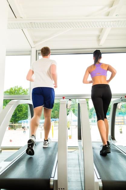 Pessoas no ginásio de esporte na esteira correndo Foto Premium