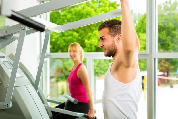 Pessoas no ginásio de esporte na máquina de fitness Foto Premium