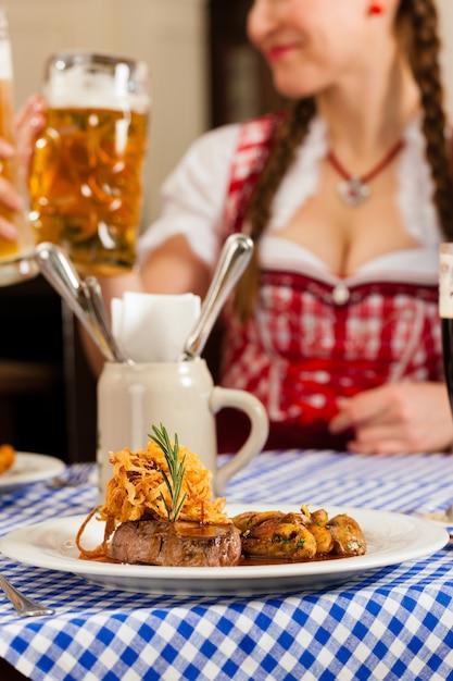 Pessoas no tradicional tracht da baviera comendo no restaurante ou pub Foto Premium