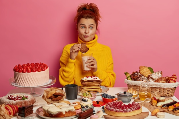 Pessoas, nutrição, calorias, conceito de padaria. a garota gengibre de macacão amarelo come saborosos biscoitos de aveia e bebe iogurte, senta à mesa com muitos bolos deliciosos, não mantém a dieta. Foto gratuita