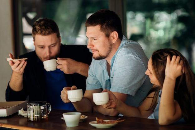 Pessoas pensativas, tomando café e comendo pizza no café Foto gratuita
