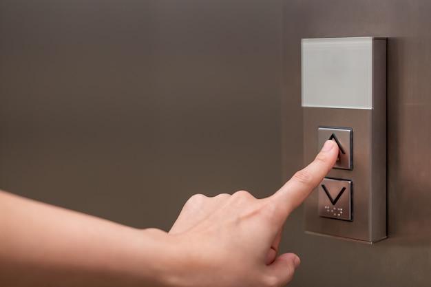 Pessoas pressionando o botão no elevador e selecione o primeiro andar usando o dedo indicador. Foto Premium