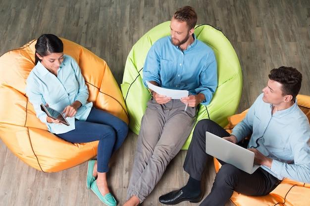 Pessoas que discutem questões comerciais em cadeiras beanbag Foto gratuita