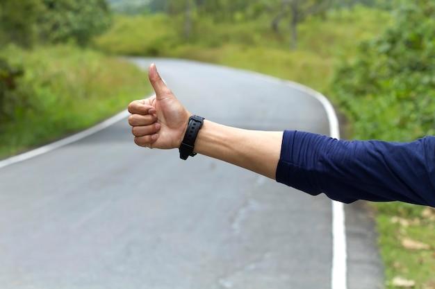 Pessoas que mostram carona na estrada Foto Premium
