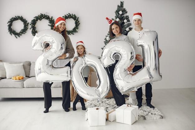 Pessoas reparando pelo natal. pessoas com balões 2021 / família descansando em uma sala festiva. Foto gratuita