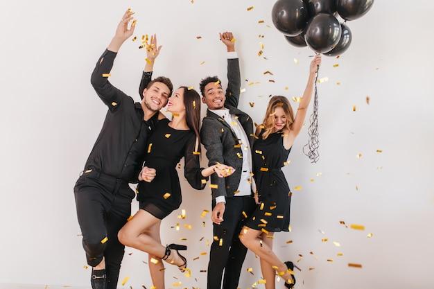 Pessoas se divertindo na festa com balões pretos e confetes Foto gratuita