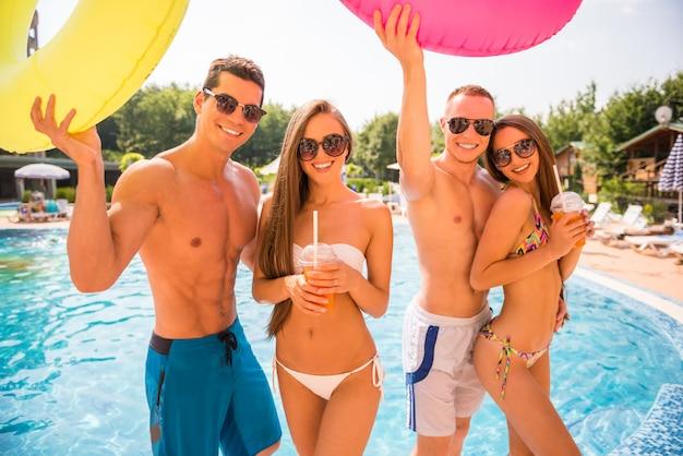 Pessoas se divertindo na piscina com anéis de borracha coloridos Foto Premium