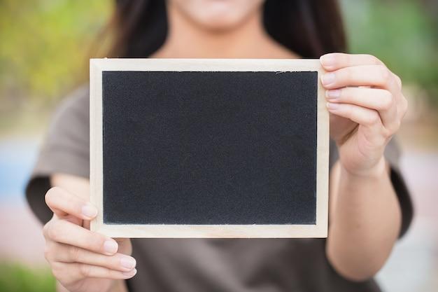 Pessoas seguram lousa vazia, quadro de giz com giz no espaço da escola para texto de giz Foto Premium