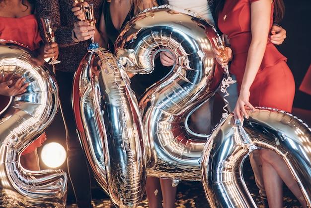 Pessoas segurando balões em forma de números do novo ano 2020 Foto Premium