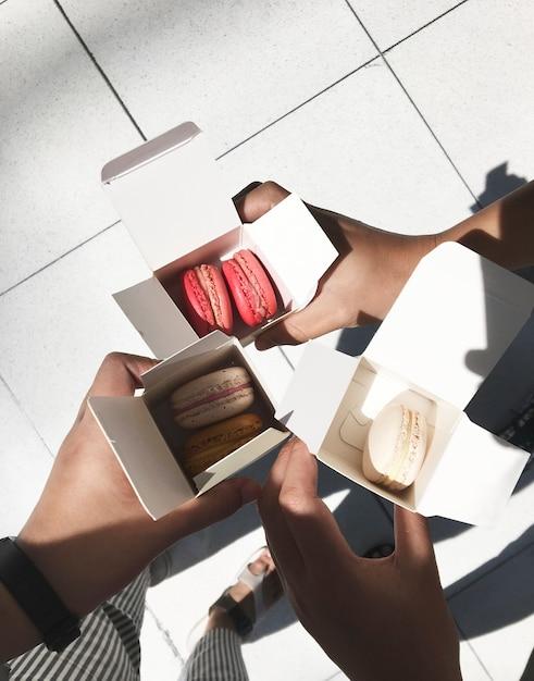 Pessoas segurando macarons na caixa Foto gratuita