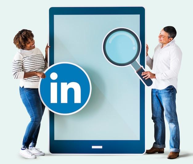 Pessoas segurando um ícone do linkedin e um tablet Foto gratuita