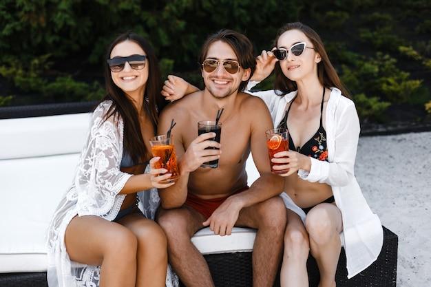 Pessoas sentadas na espreguiçadeira com coquetel nas mãos Foto Premium