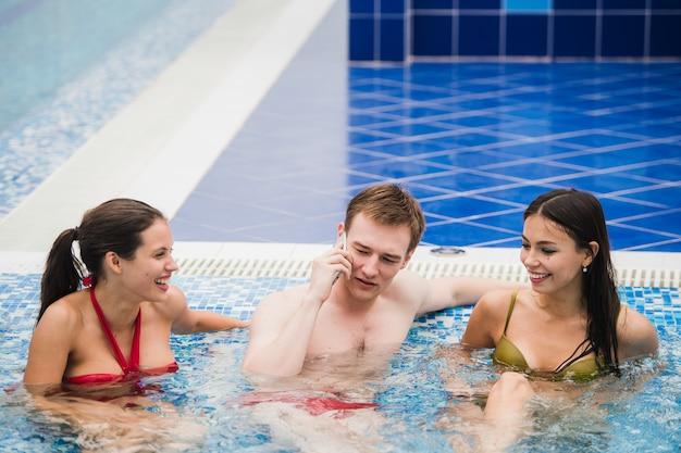 Pessoas sorridentes com telefone celular na piscina fazendo ligação. conceito de saúde, relaxamento e comunicação Foto Premium