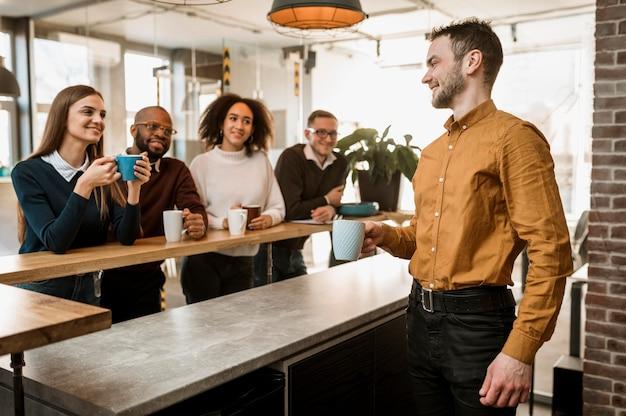 Pessoas sorridentes tomando café durante uma reunião Foto gratuita
