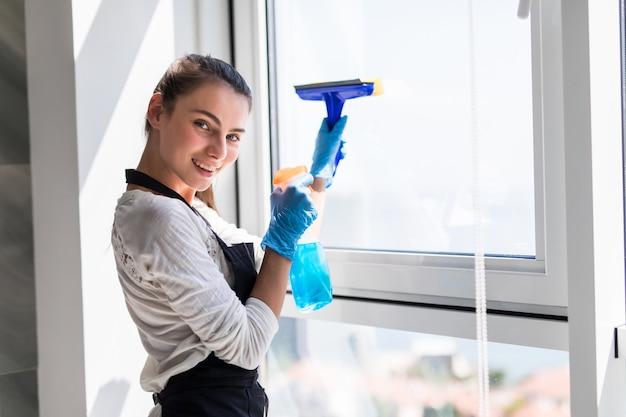 Pessoas, tarefas domésticas e conceito de limpeza. mulher feliz em luvas de janela de limpeza com pano e spray de limpeza em casa Foto gratuita