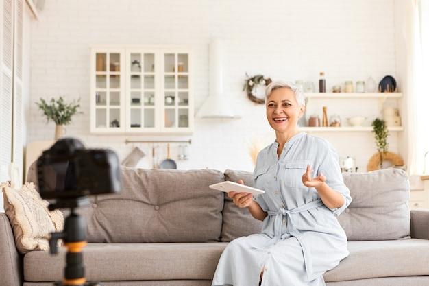 Pessoas, tecnologia e conceito de aparelhos eletrônicos modernos. foto de uma linda blogueira sênior de cabelo curto, sentada no sofá no interior da cozinha, usando tablet digital Foto gratuita