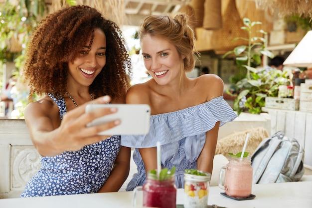 Pessoas, tempo de lazer e recreação. alegre mulher afro-americana e sua melhor amiga passam o tempo livre no café, fazem selfie no celular, bebem smoothie. conceito de relacionamentos multiétnicos Foto gratuita