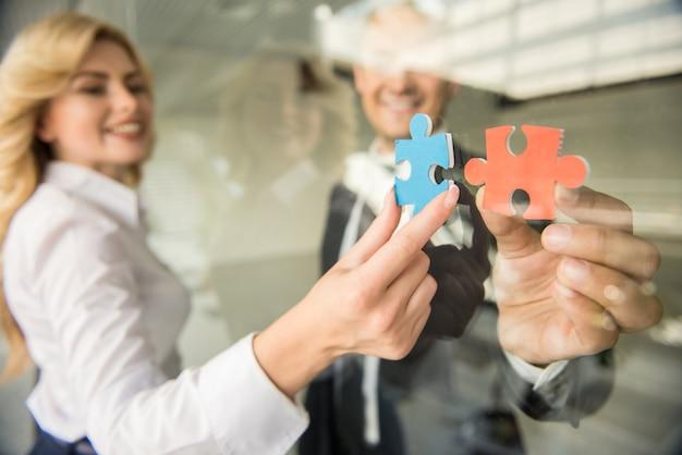 Pessoas tentando conectar pequenos pedaços de quebra-cabeça no escritório. Foto Premium