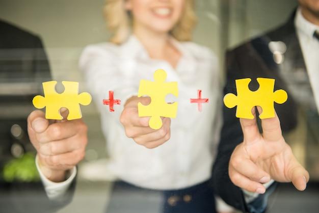 Pessoas tentando conectar pequenos pedaços de quebra-cabeça. Foto Premium