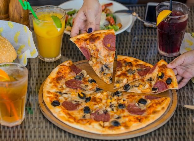 Pessoas tomando fatias de pizza de pepperoni de azeitona Foto gratuita